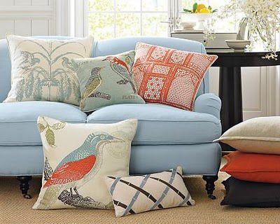 Sofá azul claro com almofadas com estampas de pássaros.