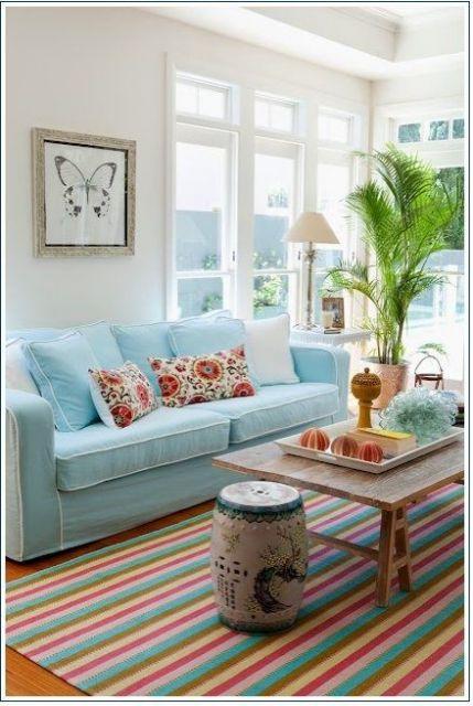 Sala de estar com sofá claro e tapete listrado.