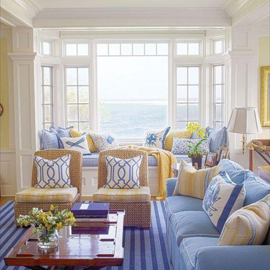 Sala com sofá azul e poltronas com tons neutros.