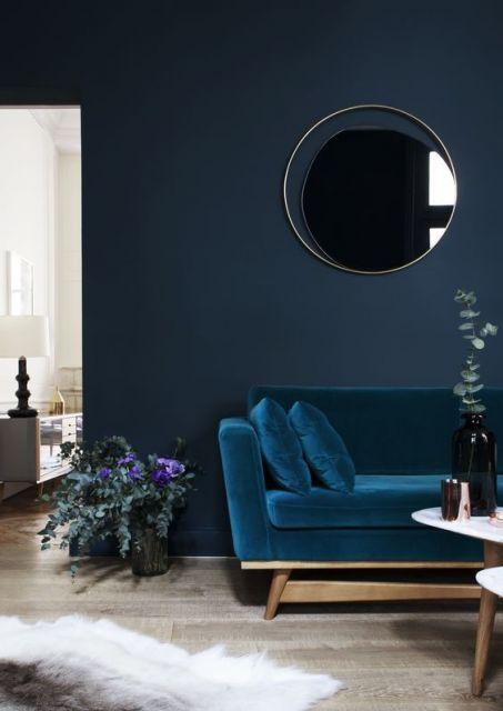 Sala com parede escura e sofá azul escuro.