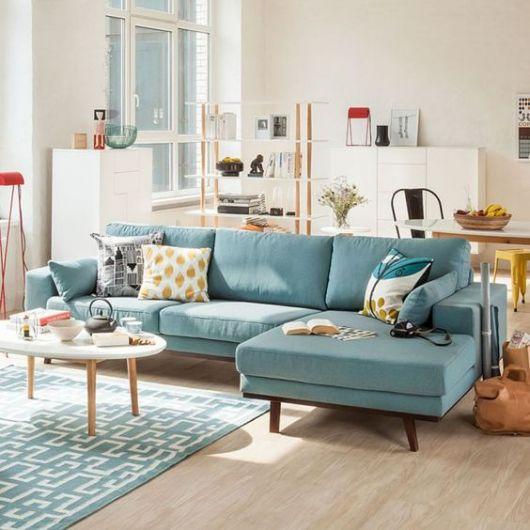Sofá azul de três lugares no meio de sala.