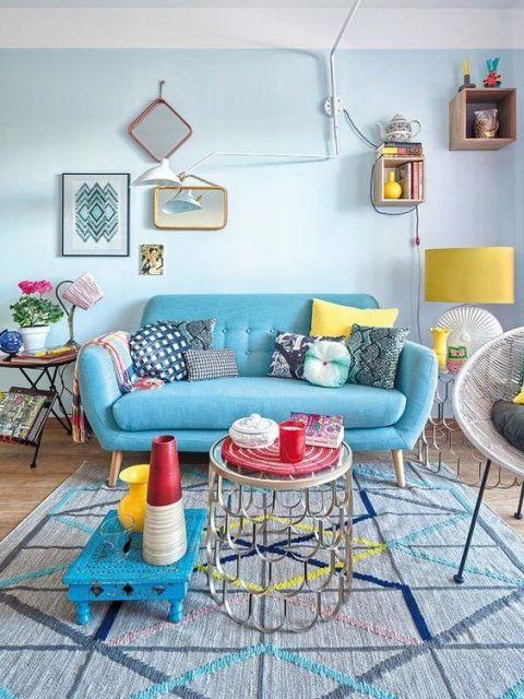 Sofá azul turqueza com almofadas e outros itens decorativos coloridos.