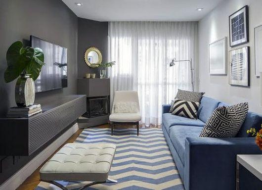 Sofá azul em sala com tons neutros e pastéis.