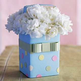 Vaso azul claro com laço e bolinhas coloridas.