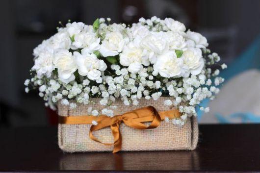 Vaso de caixa de leite com flores brancas.