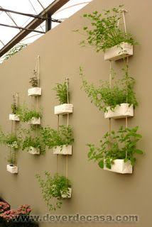 Caixas de leite penduradas em muro com plantas.