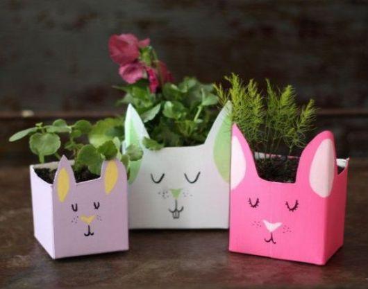 Três vasos, um rosa, um lilás e um branco, com desenhos de gato.