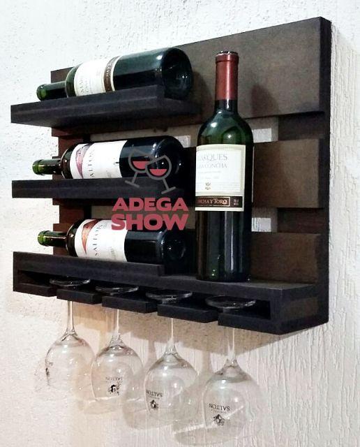 Adega de parede feita de madeira com quatro garrafas de vinho e quatro taças posicionadas de ponta cabeça na parte inferior