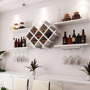 Adega de parede dividida em cinco parte. No centro há um local onde as garrafas podem ser inseridas horizontalmente e nos cantos há pequenas prateleiras que comportam as garrafas e as taças.
