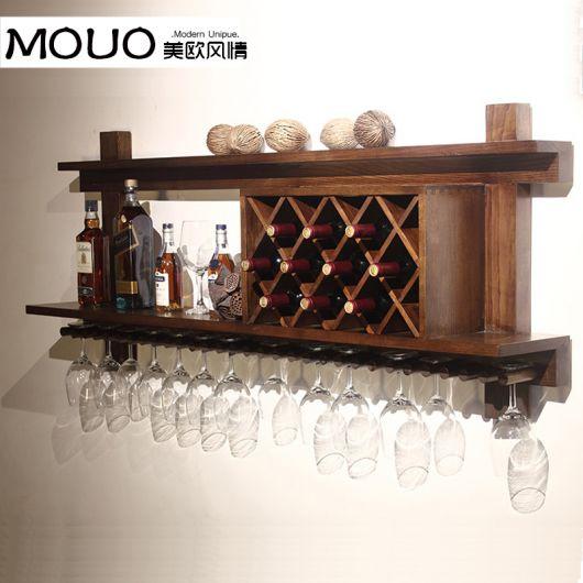 Adega de parede grande feita de madeira com muitas garrafas e taças em seu interior