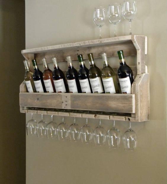 Adega de parede feita com pallet que acomoda muitas taças e 10 garrafas de vinho