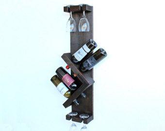 Adega de parede feita de madeira que dá suporte para quatro garrafas e quatro taças