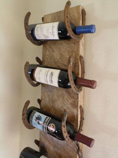 Adega de parede feita a partir de uma madeira e ferradas. A cada duas ferraduras, é possível posicionar uma garrafa.