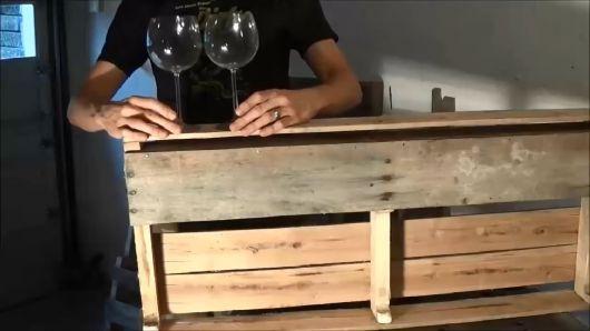 Homem segurando duas taças de vinho apoiadas em um palete