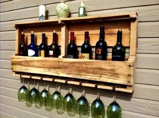 Adega de parede feita de pallets com taças e garrafas inseridas nela