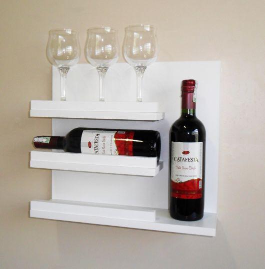 Adega de parede com duas garrafas de vinho, uma na horizontal e outra na vertical, e três taças apoiadas na parte superior.