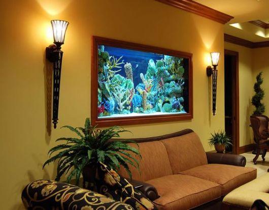 Aquário de parede muito bem decorado acima de um sofá em um cômodo com bastante plantas