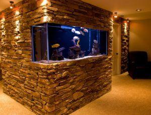 Aquário de parede instalado em uma parede toda feita de pedras