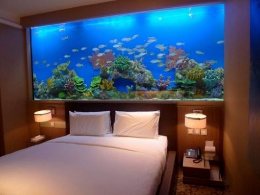 Aquário de parede grande com muitos peixes que fica logo acima da cabeceira da cama