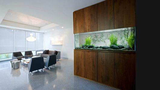 Aquário de parede instalado em um espaço de trabalho que possui uma mesa de reunião e muitas cadeiras em volta