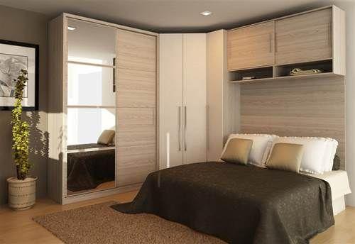 Quarto de casal com armários em madeira clara.