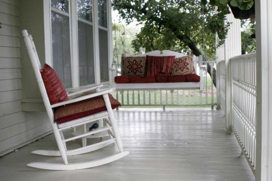varanda de madeira cadeira de balanço branca