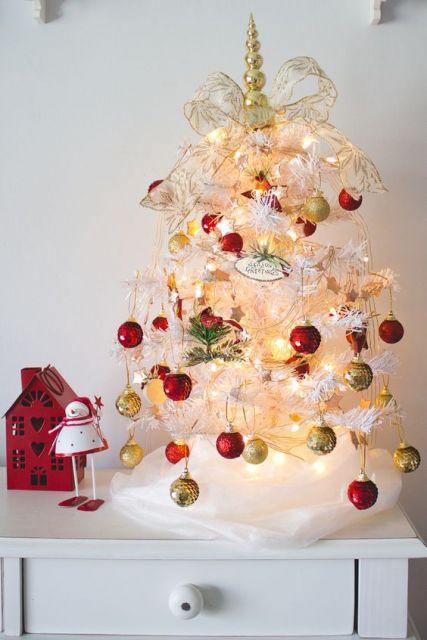 Árvore de Natal branca sobre móvel.