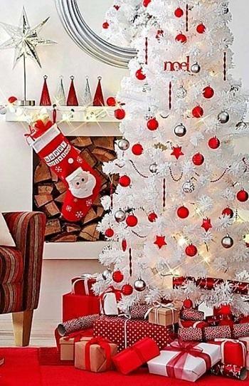 Meia pendurada na lareira e árvore de Natal branca com bolas vermelhas e prateadas.