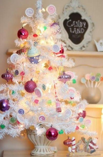 Árvore de Natal branca pequena com enfeites rosa e lilás.