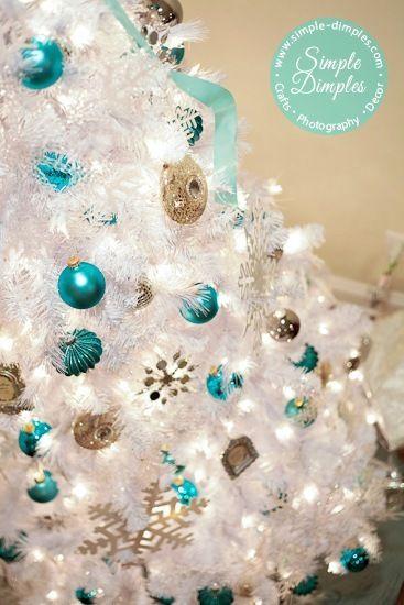 Árvore branca com enfeites azuis e dourados e luz de LED.