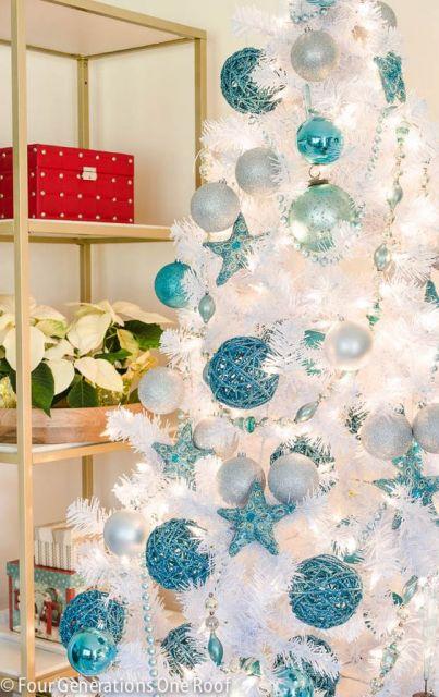 Árvore branca com bolas e estrelas azuis.