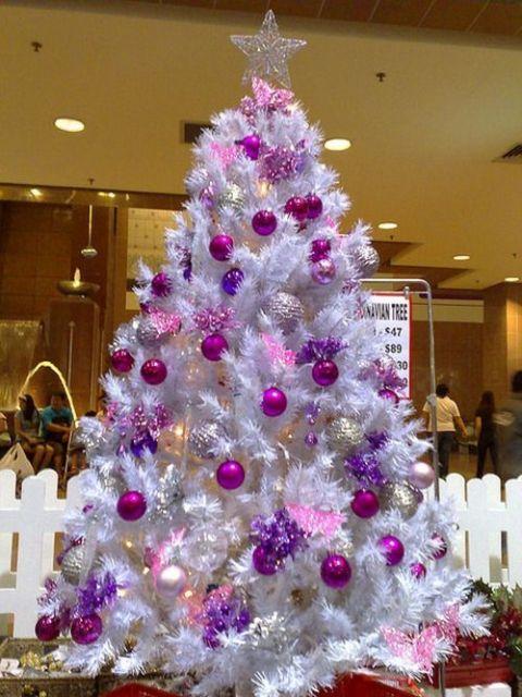 Árvore branca com enfeites rosa e roxo.