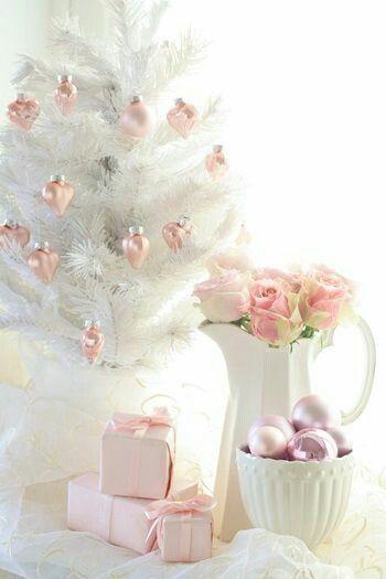 Árvore branca ao lado de jarra com flores.