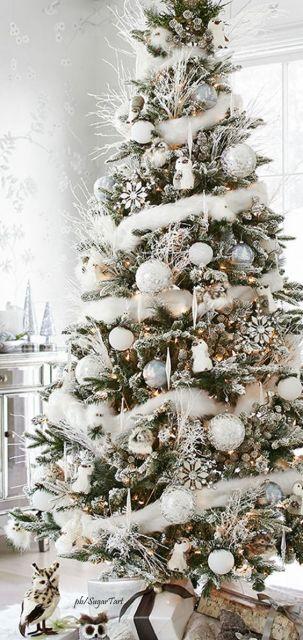 Árvore com algumas folhas verdes e decoração em branco.