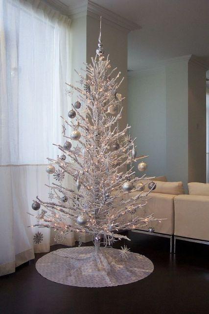 Árvore de Natal branca com bolas prateadas.