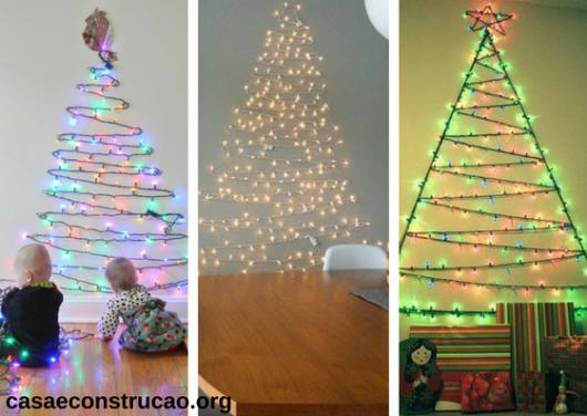 árvores de Natal diferentes feitas com luzinhas presas na parede