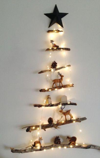 árvore de Natal na parede feita com gravetos e decorada com miniaturas de renas