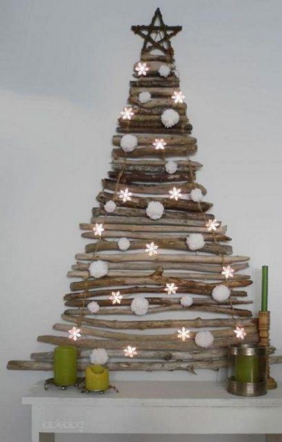 árvore de Natal na parede sobre móvel feita com gravetos