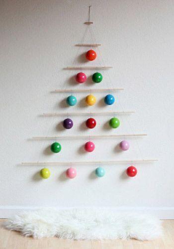árvore de Natal na parede feita com uma varalzinho e decorado com bolas coloridas
