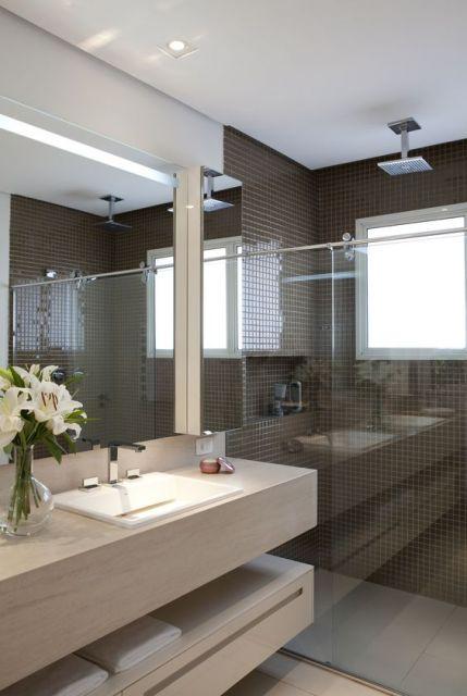 Banheiro com azulejos marrom e pia bege.