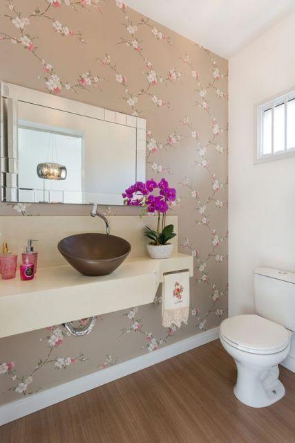Banheiro branco com uma parede marrom com desenhos.