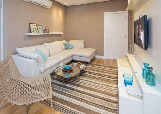 Sala com tapete listrado, parede marrom e sofá branco.
