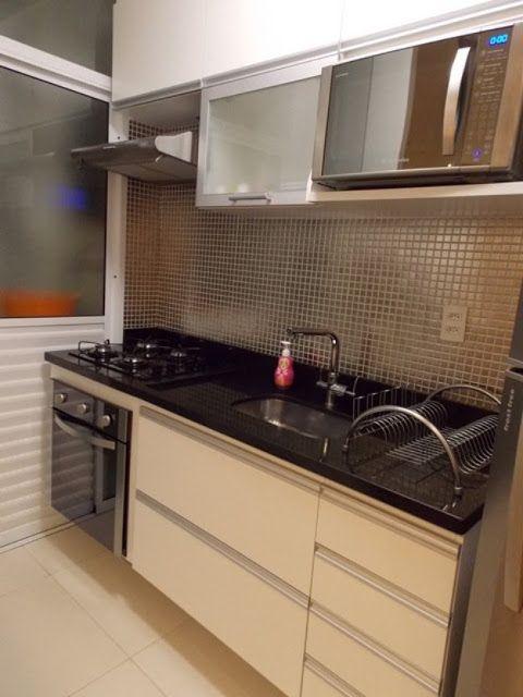 Cozinha com azulejos marrom e móveis bege.