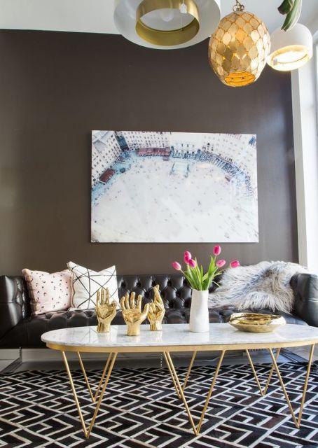 Sala com parede marrom escura, sofá preto, quadro e mesa claros.