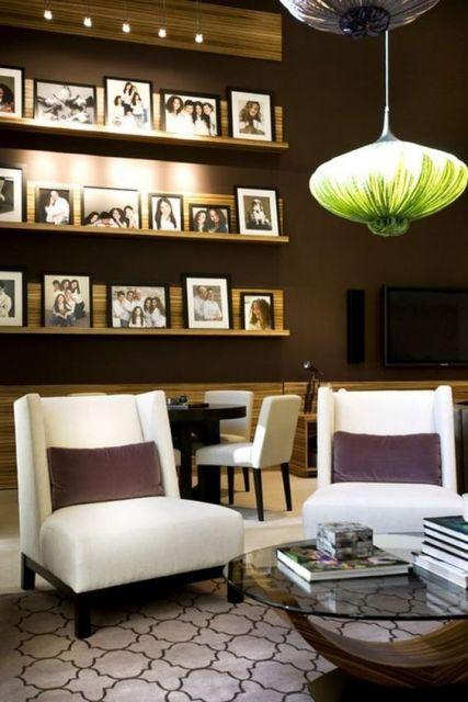 Cômodo com parede marrom, poltronas brancas e diversos porta-retratos.