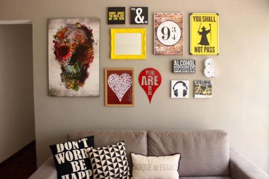 Parede com vários quadros coloridos e sofá encostado.