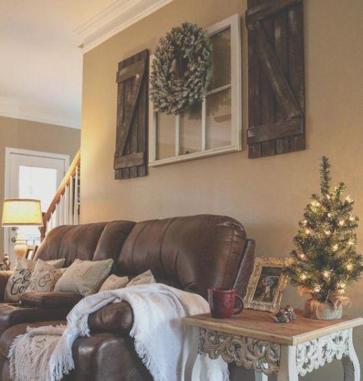 Sala com sofá de couro marrom e parede clara.