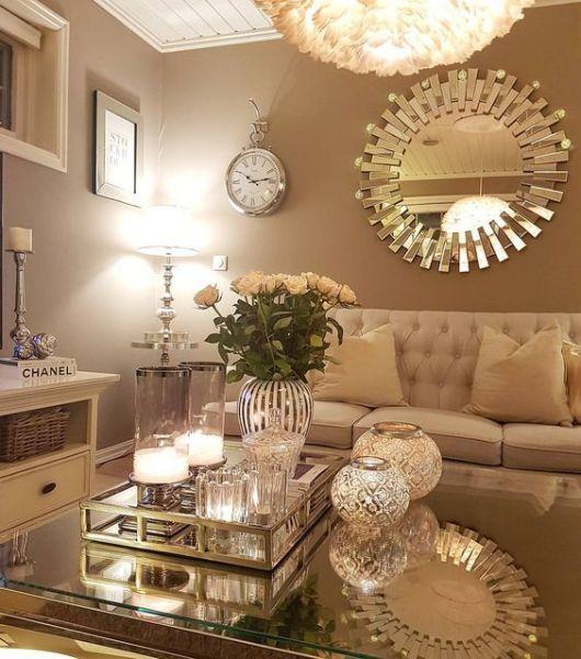 Sala com paredes marrons, com espelho e relógio pendurado.