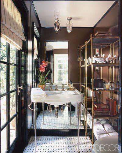 Banheiro com espelho grande e paredes escuras.
