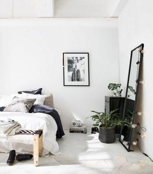 vaso preto com planta em frente ao espelho em quarto